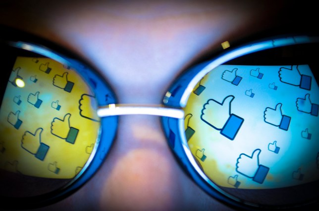 """The Facebook """"thumbs up"""" or """"lie"""" gesture is seen reflected in a pair of sunglasses on November 3, 2017. (Photo by Jaap Arriens/NurPhoto via Getty Images)"""