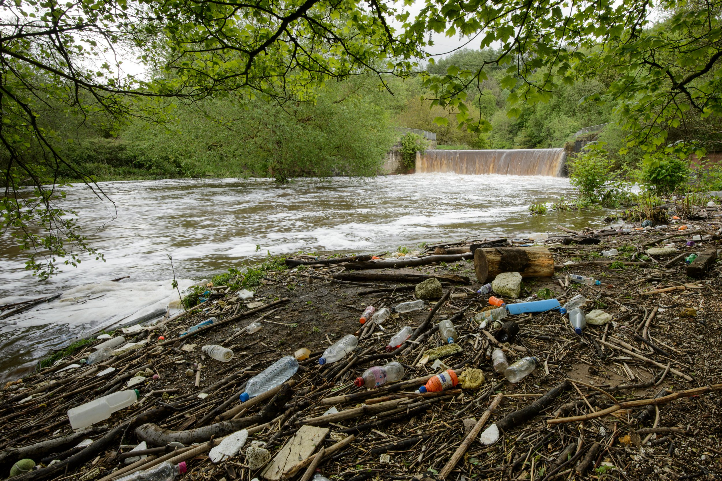 K2DCE8 Rubbish left behind by urban river in spate, River Tame, Manchester, UK May