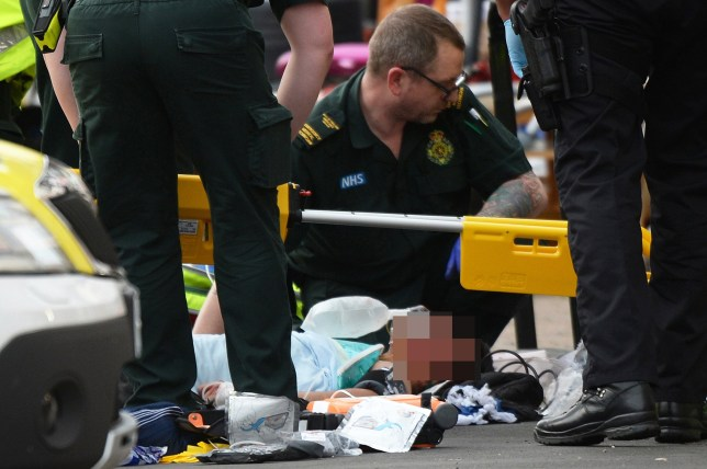 *** EXCLUSIVE *** BURY PARK, UNITED KINGDOM - MARCH 14: A man has suffered terrible injuries after a hit and run incident on March 14, 2018 in Bury Park, Luton. According to the BBC a police car was following a stolen vehicle into the heavily populated area of Luton known as Bury Park. A massive police and ambulance presence was at the scene with the seriously injured man being tended to on the pavement by both paramedics and police. A local man who did not wish to be named stated that the injured man was given CPR on the pavement. An air ambulance flew into Luton Town Football Club ready to convey the critically injured man to hospital. The car involved in the hit and run was found nearby and a cordon placed around it, then a police search dog and the force helicopter assisted a great many officers in hunting for the car occupants. It is believed they are still at large. The injured man was conveyed by ambulance to the football ground and the air ambulance. Picture shows; The paramedics and an armed policeman helping the injured man in Selbourne Road. PHOTOGRAPH BY Tony Margiocchi / Barcroft Images