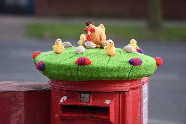 MERCURY PRESS. Liverpool, UK. 26/3/18. Pictured: The knitted display on a postbox in Liverpool this afternoon. A mystery knitter has transformed a post box into an adorable Easter scene complete with woollen grass, chicks and eggs. The colourful knitted display - with green grass, red and purple striped eggs, a hen and chicks - suddenly appeared on top of the red Royal Mail post box on Booker Avenue, Liverpool, Merseyside, this afternoon (MON). It is unknown which talented knitter is behind the delightful decoration but it has been a hit on social media with people describing it as eggsellent. SEE MERCURY COPY