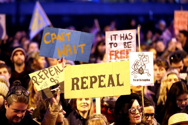 People carrying various signs, as participants take part in a march through Dublin city centre calling for the repeal of the 8th amendment to the Irish constitution.
