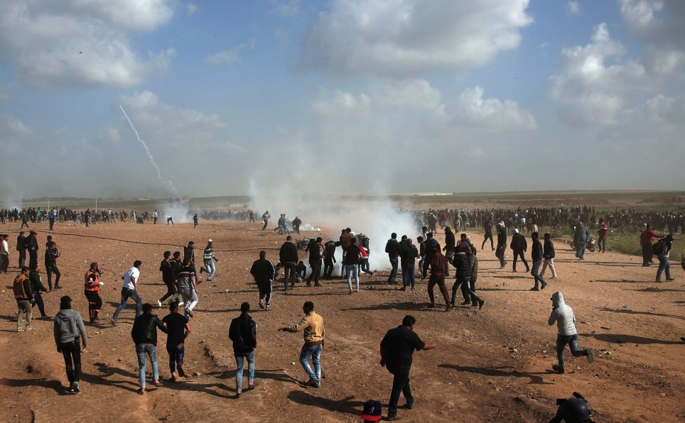 Palestinian protesters run for cover from teargas fired by Israeli troops during a demonstration near the Gaza Strip border with Israel, in eastern Gaza City, Friday, March 30, 2018. (AP Photo/ Khalil Hamra)