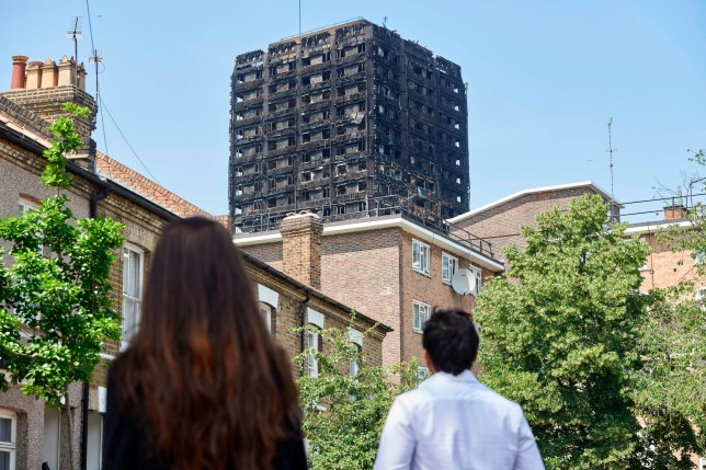 TOPSHOT - The burned-out shell of the Grenfell Tower block is seen behind terraced houses as local residents look on near the scene of the fire in North Kensington, west London on June 20, 2017. Police on June 19 revised up the toll to seventy-nine people dead or missing and presumed dead following the devastating blaze at the Grenfell Tower block. / AFP PHOTO / NIKLAS HALLE'N (Photo credit should read NIKLAS HALLE'N/AFP/Getty Images)
