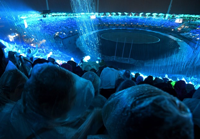 Spectators sit in the rain as they wait for the start of the opening ceremony of the 2018 Gold Coast Commonwealth Games at the Carrara Stadium on the Gold Coast on April 4, 2018. / AFP PHOTO / FRANCOIS XAVIER MARITFRANCOIS XAVIER MARIT/AFP/Getty Images