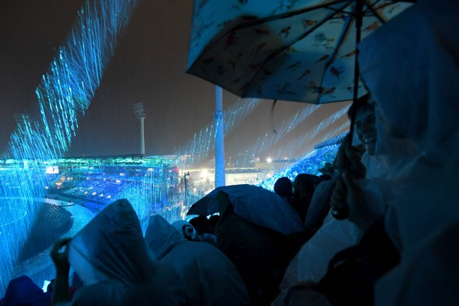 Spectators wear raincoats as they watch the opening ceremony of the 2018 Gold Coast Commonwealth Games at the Carrara Stadium on the Gold Coast on April 4, 2018. / AFP PHOTO / FRANCOIS XAVIER MARITFRANCOIS XAVIER MARIT/AFP/Getty Images