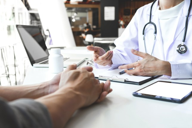 Healthcare and Medical concept, patient listening intently to a female doctor explaining patient symptoms or asking a question as they discuss paperwork together in a consultation.