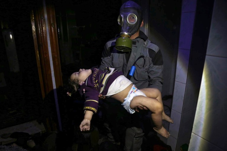 EDS NOTE: GRAPHIC CONTENT - This image released early Sunday, April 8, 2018 by the Syrian Civil Defense White Helmets, shows a rescue worker carrying a child following an alleged chemical weapons attack in the rebel-held town of Douma, near Damascus, Syria. Syrian rescuers and medics say a poison gas attack on Douma has killed at least 40 people. The Syrian government denied the allegations, which could not be independently verified. The alleged attack in the town of Douma occurred Saturday night amid a resumed offensive by Syrian government forces after the collapse of a truce. (Syrian Civil Defense White Helmets via AP)