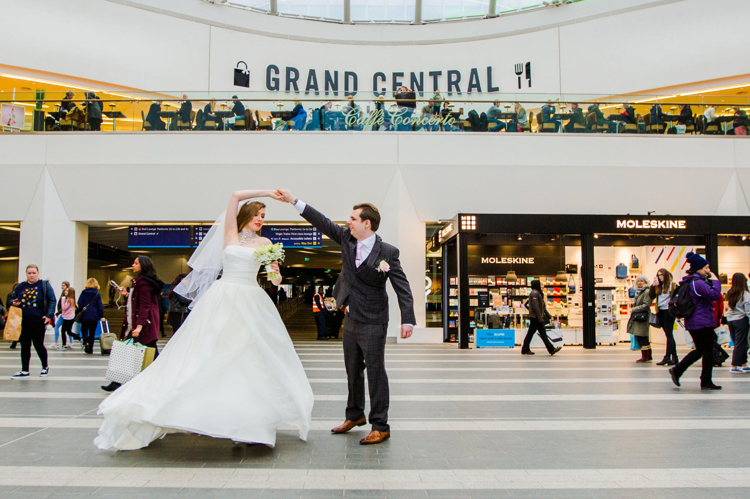 It was a wedding train with a difference - when a couple of newlyweds posed for their marriage photos in the shopping centre above New Street station. See NTI story NTIWED. Alex and Luke Jarrett wanted to remember their big day with some pictures that were out of the ordinary. So they secured permission to use the giant Grand Central mall in Birmingham city centre as the backdrop for their snaps. The couple mingled with amazed shoppers and passengers as they became the first to use the showpiece centre for wedding photos. The photo shoot with a difference happened last Saturday, after Alex and Luke, from Stafford, married at the Burlington Hotel. Once the formalities were over, the couple and their bridesmaids and groomsmen trooped through the city centre for their snaps with their wedding photographer, who wanted to be known only as Aaron.