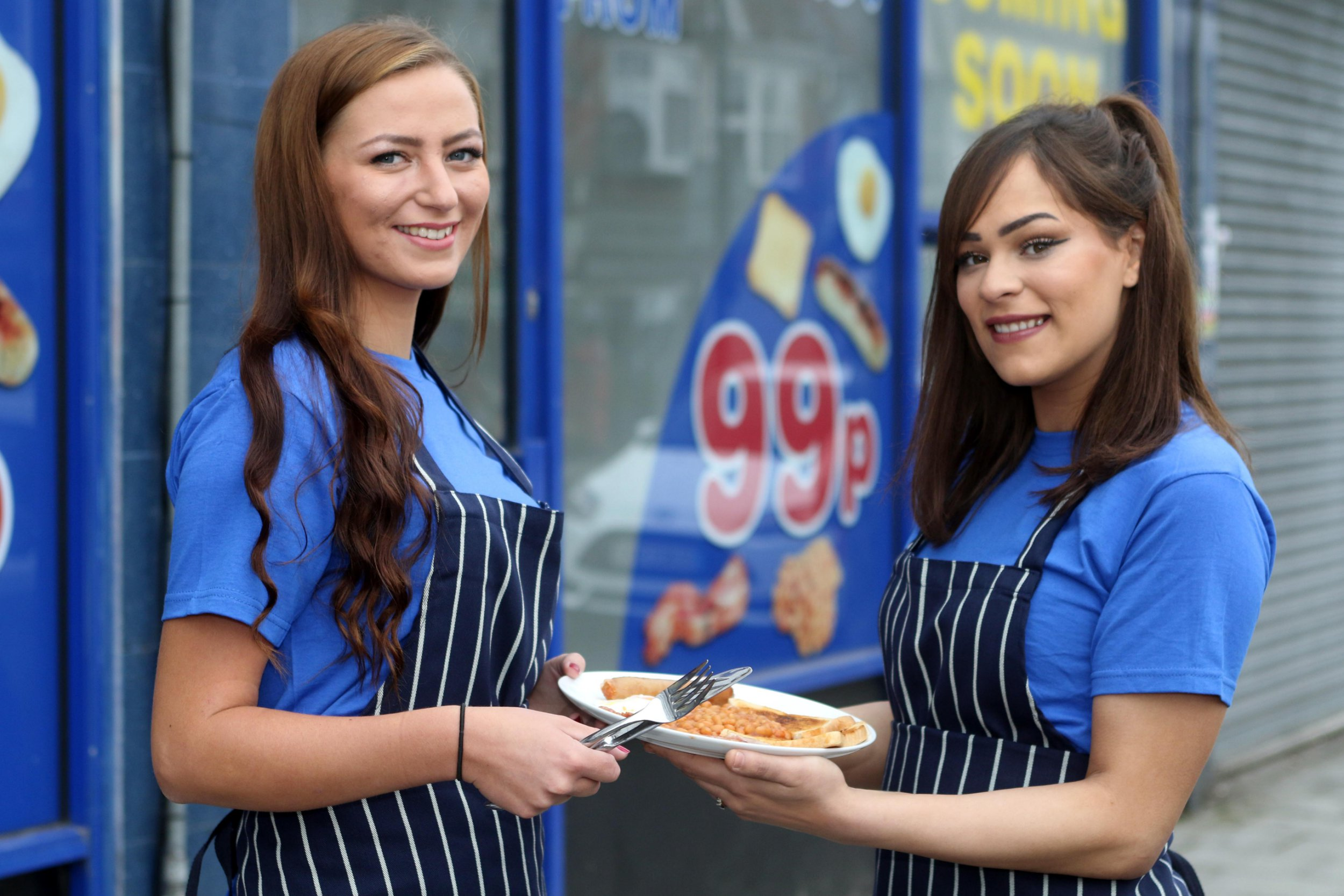 Date: April 10 2018 Location: Southend, Essex, England. A caf?? selling what could be Britain???s cheapest fry-up for just 99p is hitting the High Street. The Grafters Cafe, in Southend, Essex will target tradesman as well as striving families ??? billing itself as the ???Poundland??? of restaurants. Pictured: (l-r) Waitresses Jess Kavanagh (left) and Sophia Stanford, both 22 outside the cafe. Words: Essex News and Pictures.