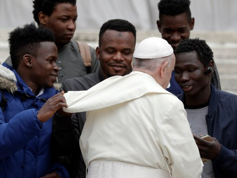 Migrant pictured pulling Pope Francis's cape was actually helping him