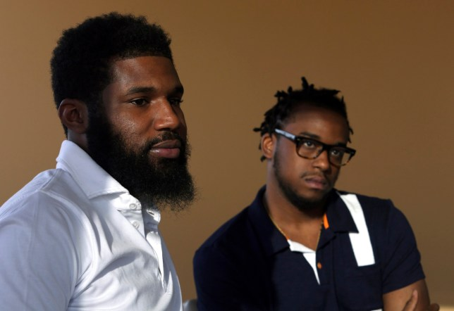 In this Wednesday, April 18, 2018 photo, Rashon Nelson, left, and Donte Robinson, right, listen to a reporter's question during an interview with The Associated Press in Philadelphia. Their arrests at a local Starbucks quickly became a viral video and galvanized people around the country who saw the incident as modern-day racism. In the week since, Nelson and Robinson have met with Starbucks CEO Kevin Johnson and are pushing for lasting changes to ensure that what happened to them doesn't happen to future patrons. (AP Photo/Jacqueline Larma)