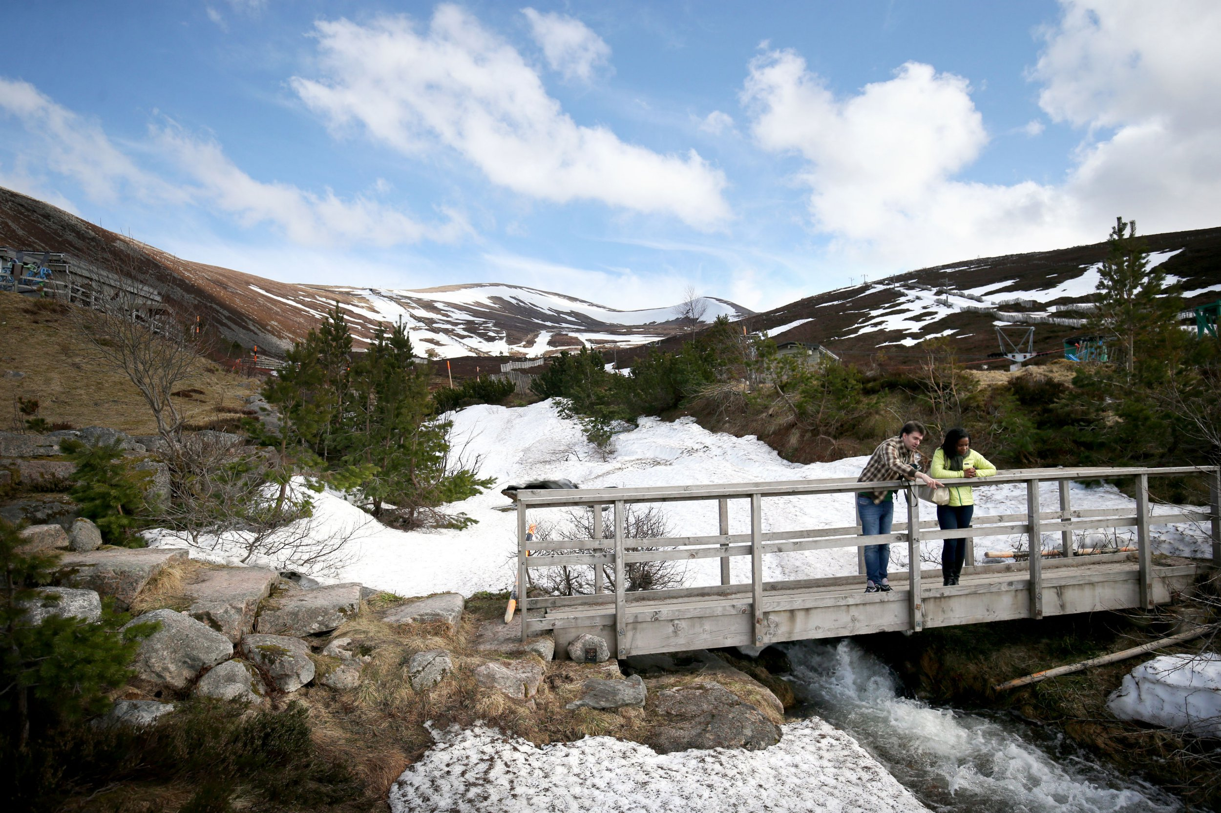 Visitors on a bridge next to one of the few remaining patches of snow on the Cairngorm Mountain near Aviemore, Scotland. PRESS ASSOCIATION Photo. Picture date: Thursday April 19, 2018. Photo credit should read: Jane Barlow/PA Wire