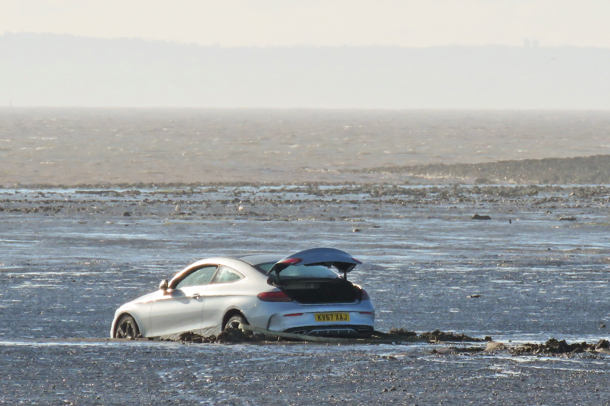 PIC: BURNHAM-ON-SEA.COM/APEX 23/04/2018 A top range motor that got stuck on a notorious beach had a tragic outcome. A man working for a commercial vehicle recovery service died on Brean beach, Somerset on Sunday after suffering a heart attack while attempting to retrieve a stranded Mercedes car from the mud. An air ambulance also flew in to help him and several Burnham-On-Sea Coastguards, paramedics, first aiders and a nurse attempted to revive the man by giving him CPR after he collapsed during the car recovery operation. It comes after a Mercedes hire car had initially become stuck on Brean beach on Saturday evening after being driven half a mile down the beach near Brean Down. Crews were unable to winch the car to safety on Saturday and therefore on Sunday a Bridgwater-based vehicle recovery company attempted to retrieve the vehicle on behalf of the hire car firm. One of the workers collapsed during the work. ** SEE STORY BY APEX NEWS - 01392 823144 ** ---------------------------------------------------- APEX NEWS AND PICTURES NEWS DESK: 01392 823144 PICTURE DESK: 01392 823145