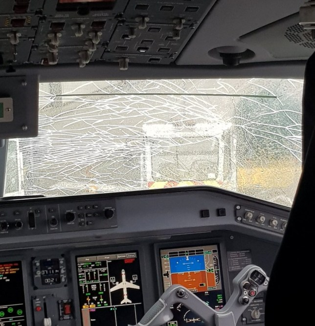 This dramatic picture shows the cracked windscreen of a Flybe plane that was damaged just minutes after take-off. See SWNS story SWCRACKED: The flight from Newquay Airport to London Gatwick was forced to turn back and land when a huge crack spanning across the main cockpit window suddenly appeared. Ray Ellis, 40, from Helston, Cornwall, was one of the 92 passengers who were on board the 7.25am flight on Tuesday and as he left took a picture inside the cockpit. The pilot had left the door to the cabin open as people disembarked so that they could see for themselves the problem that had forced them to return to the ground.