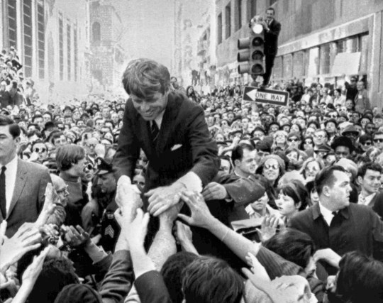"FILE - In this April 2, 1968 file photo U.S. Sen. Robert F. Kennedy, D-NY, shakes hands with people in a crowd while campaigning for the Democratic party's presidential nomination on a street corner, in Philadelphia. Nearly 50 years after Robert F. Kennedy's assassination, a new documentary series on his life and transformation into a liberal hero is coming to Netflix. ""Bobby Kennedy for President"" produced by RadicalMedia, Trilogy Films and LooksFilm launches Friday, April 27, 2018, on Netflix. (AP Photo/Warren Winterbottom, File)"