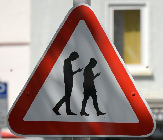 Mandatory Credit: Photo by APA-PictureDesk GmbH/REX/Shutterstock (9642874d) A road sign warning motorists that people are likely to cross the road whilst checking thier phones outside the Friedrich-List-Gymnasium school is to be removed as it was put up unofficially. Road sign warning motorists of people crossing the road whilst looking at their phones, Reutlingen, Germany - 25 Apr 2018