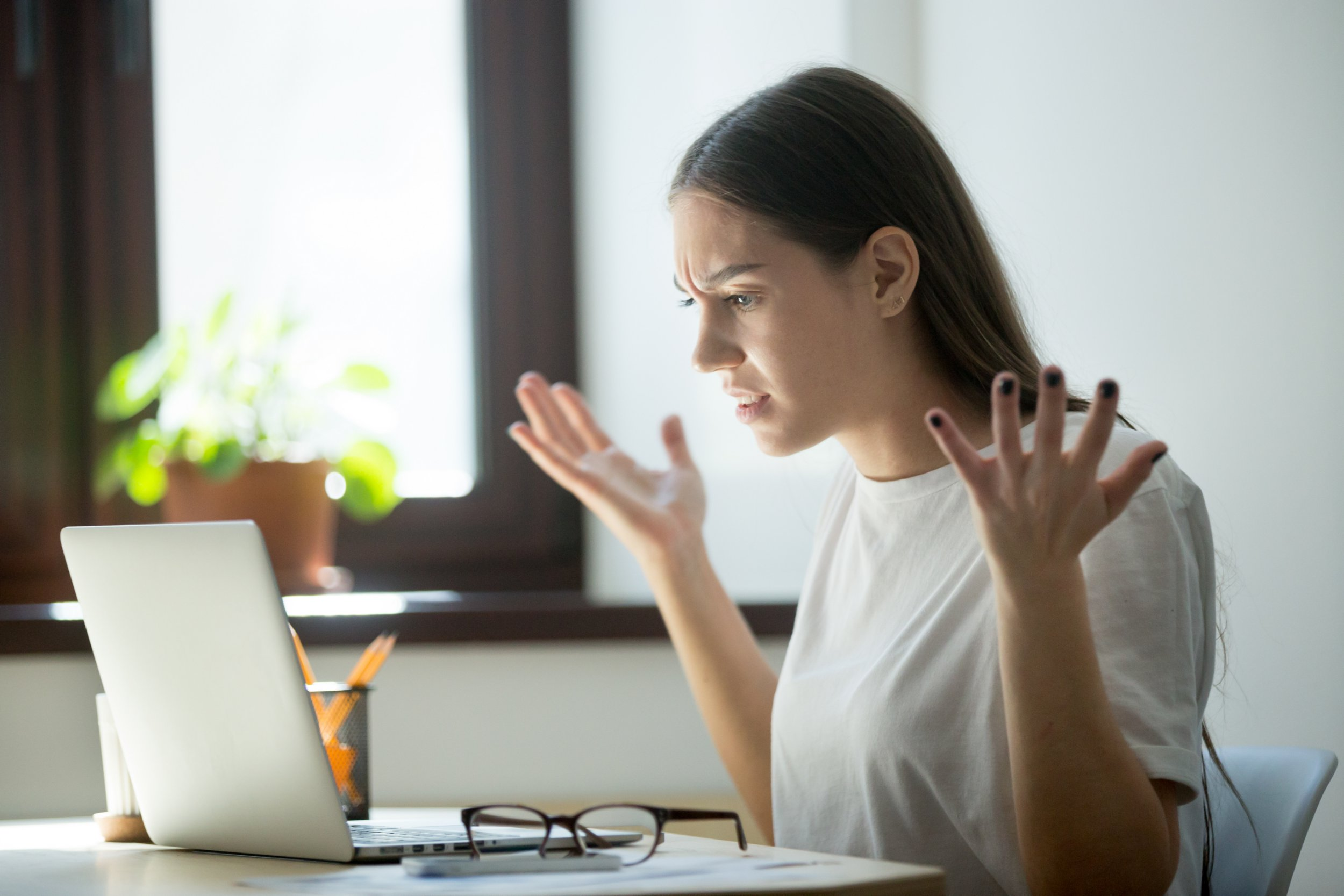 Millennial generation young adult woman looking in laptop computer, fling arms up. She just found mistake in last assignment, error in contract, disagreement in email or dissatisfied buyer message.; Shutterstock ID 725378587; Purchase Order: -