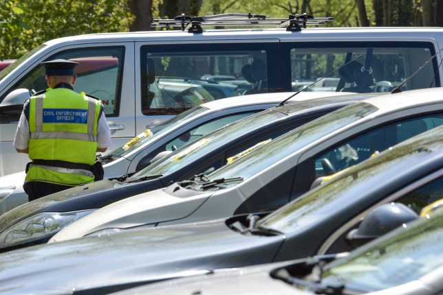 Pic by Michael Scott/Caters News - (PICTURED: A Civil Enforcement Officer places another ticket on a vehicle in a coaches only area of Cannon Hill Park. Twenty-three drivers were also caught out and fined in total. Pic taken 05/05/2018) - Families were struck with fines today when they left their cars to enjoy the sultry weather on the bank holiday. With temperature rising to 28 degrees, this May bank holiday has been one of the hottest on record. But for these unlucky motorists, the day has been marred by a 50.00 pound parking fine. SEE CATERS COPY