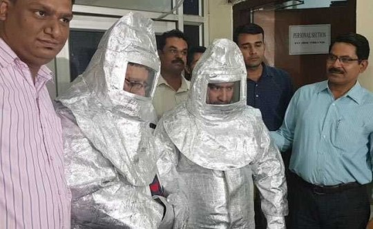 """In this photograph released by the Delhi Police on May 9, 2018, Indian officials stand alongside two men dressed in 'space suits' who were arrested for alleged fraud, after claiming to work for NASA, in New Delhi. The two men reportedly tried to sell a metal plate to a businessman by claiming it could then be sold to NASA for a higher price. / AFP PHOTO / Delhi Police / Handout / AFP PHOTO / DELHI POLICE -----EDITORS NOTE---- RESTRICTED TO EDITORIAL USE MANDATORY CREDIT """"AFP PHOTO / DELHI POLICE"""" ---- NO MARKETING NO ADVERTISING CAMPAIGNS NO ARCHIVES - DISTRIBUTED AS A SERVICE TO CLIENTSHANDOUT/AFP/Getty Images"""