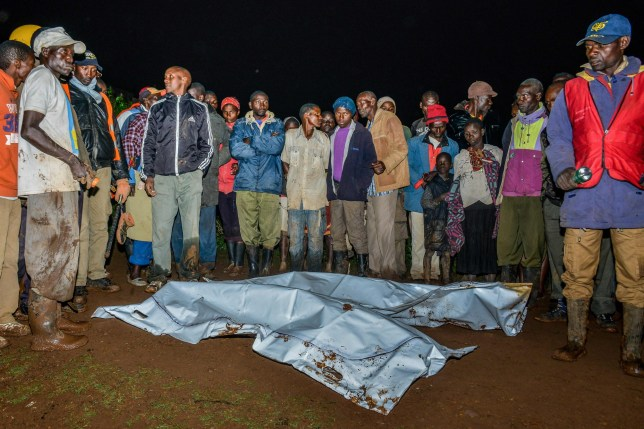 People gather around victim's bodies at a residential area after Patel dam burst its bank at Solai, about 40 kilometres north of Nakuru, Kenya, on May 10, 2018. / AFP PHOTO/AFP/Getty Images