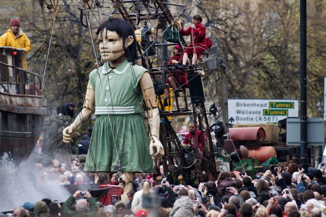 Little Girl Giant, a 30-foot high puppet, walking through crowds on Lime Street in the centre of Liverpool as part of the Sea odyssey Giant Spectacular. The three-day event, which features two giants ran from 20-22 April and attracted tens of thousands of spectators to the city's streets. The event is staged by Royal De Luxe, a company made up of actors, areialists, engineers, inventors, technicians, metal-workers and poets and was founded in Toulouse, france in 1979. (Photo by Colin McPherson/Corbis via Getty Images)