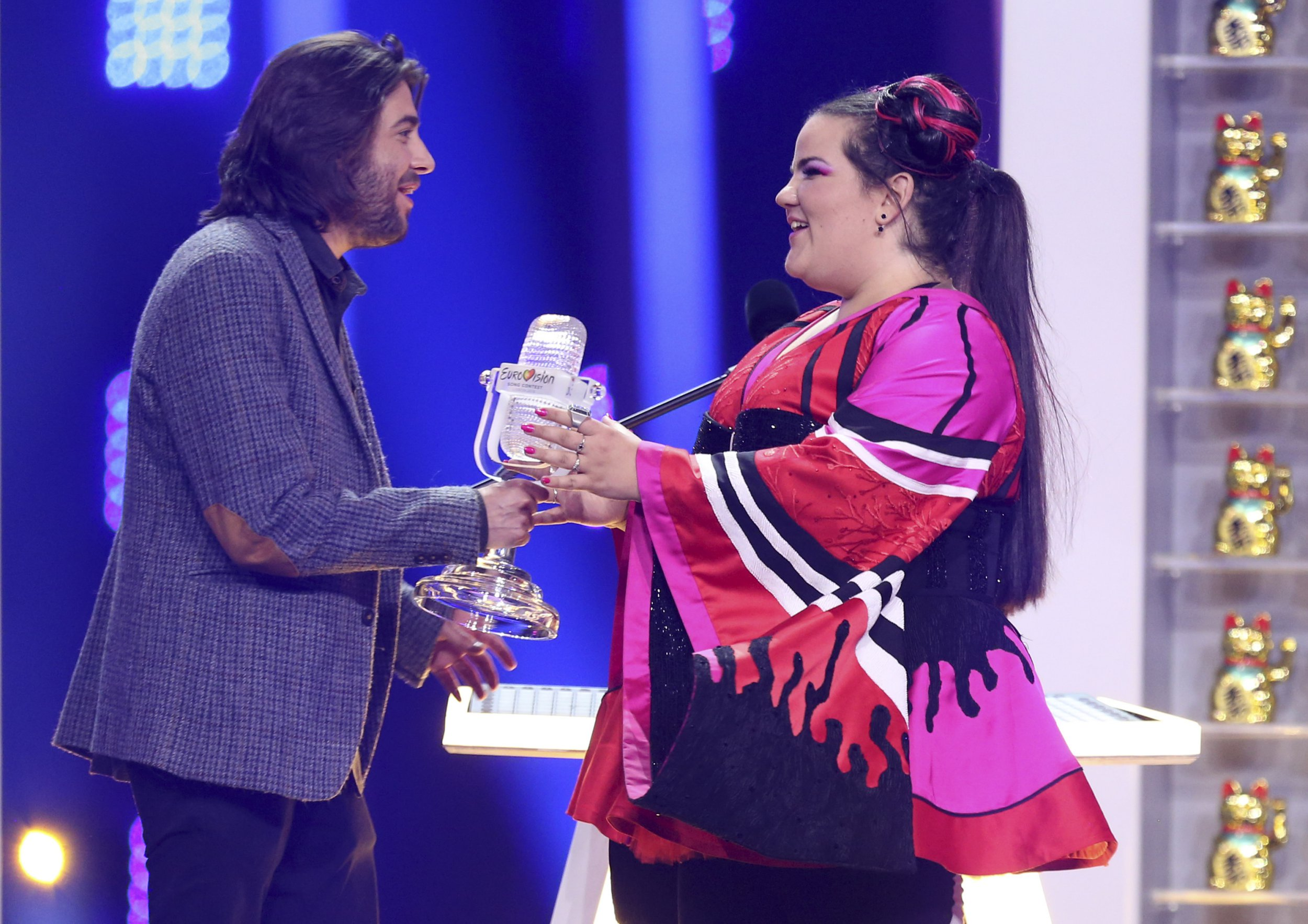 Netta from Israel, right, receives the trophy by Salvador Sobral after winning the Eurovision song contest in Lisbon, Portugal, Saturday, May 12, 2018 during the Eurovision Song Contest grand final. (AP Photo/Armando Franca)