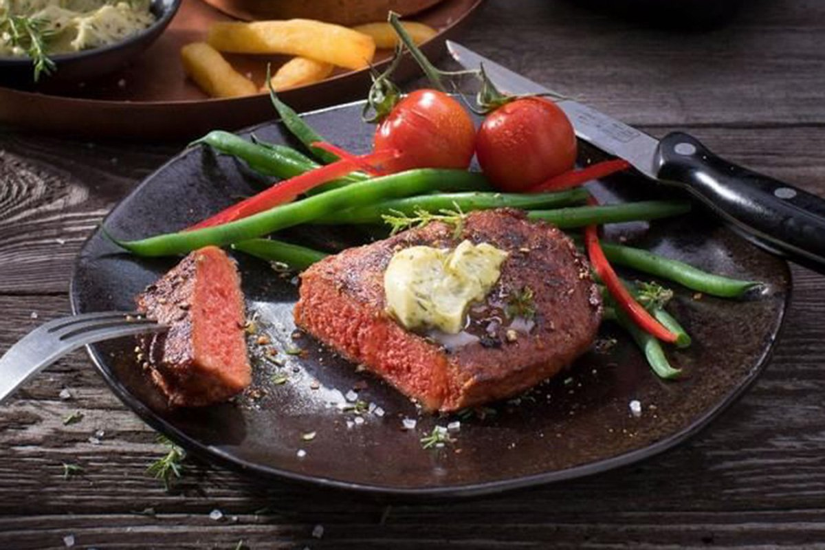 Vivera vegan steak on a plate with sauce and vegetables