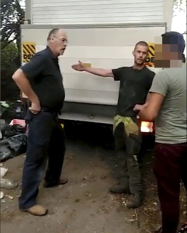 The alleged fly tipper (man on right) at Kensworth, Beds being confronted by workmen (two men on the left). See Masons copy MNFLYTIP: This is the moment five heroic workmen confronted a gang of alleged fly-tippers they caught red-handed dumping rubbish on a quiet country lane. Tree surgeon Callum Chase, 25, and brother Connor, 23, spotted three men unloading mattresses and chairs from a van as they drove home along a country road. The brothers stopped and confronted the men who denied they were doing anything wrong. The brothers, then joined by their boss and two other passing workmen, used their vans to box in the fly-tippers while they called the police.