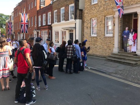 Royal fans form a very British queue to take photos with cardboard Harry and Meghan