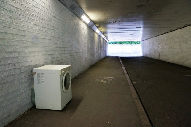 "The art installation in Oxford by @Athirty4. See SWNS story SWWASHER; A street artist who left a washing machine in an underpass will see it removed - after the council branded it FLYTIPPING. The washer was abandoned by local artist Athirty4 next to a clothes hook on which passersby are asked to ""hang their sorrows"". The washing machine, removed by council workers yesterday (Thurs), sat next to a sign referencing ""preconceptions"" about modern art in Littlemore, Oxford. Tom Hayes, the city council's greener environment boss, said: ?The washing machine is blocking the public highway."