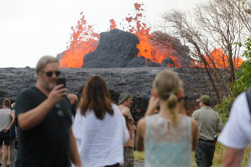 In a Saturday, May 26, 2018 photo, area residents, the media and national guard flock to what is now the end of Leilani Avenue to take in the fiery show at fissures 2, 7 and 8 of the Kilauea volcano near Pahoa. (George F. Lee/The Honolulu Advertiser via AP)