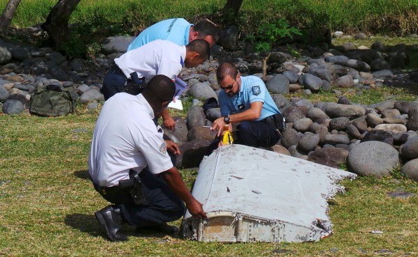 FILE PHOTO: French gendarmes and police inspect a large piece of plane debris which was found on the beach in Saint-Andre, on the French Indian Ocean island of La Reunion, July 29, 2015. REUTERS/Zinfos974/Prisca Bigot/File Photo
