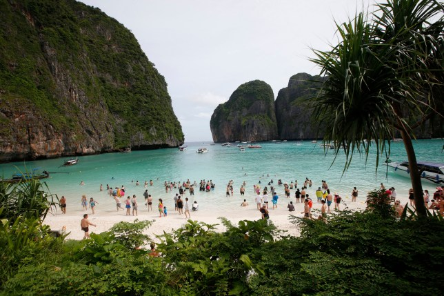 Tourists walk the beach of Maya Bay, Phi Phi Leh island in Krabi province, Thailand, Thursday, May 31, 2018. The popular tourist destination of Maya Bay in the Andaman Sea will close to tourists for four months from Friday to give its coral reefs and sea life a chance to recover from an onslaught that began nearly two decades ago. (AP Photo/Sakchai Lalit)