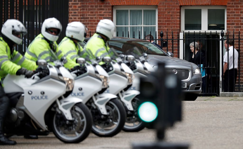 Police motorcycle outriders wait as Britain's Prime Minister Theresa May walks to her car at the rear of Downing Street in London on June 7, 2018, as she leaves on her way to the airport to travel to the G7 Summit in Canada. - British Prime Minister Theresa May is set to gather her ministers Thursday amid swirling rumours that Brexit secretary David Davis could quit over her plans to avoid a hard Irish border. (Photo by Adrian DENNIS / AFP) (Photo credit should read ADRIAN DENNIS/AFP/Getty Images)