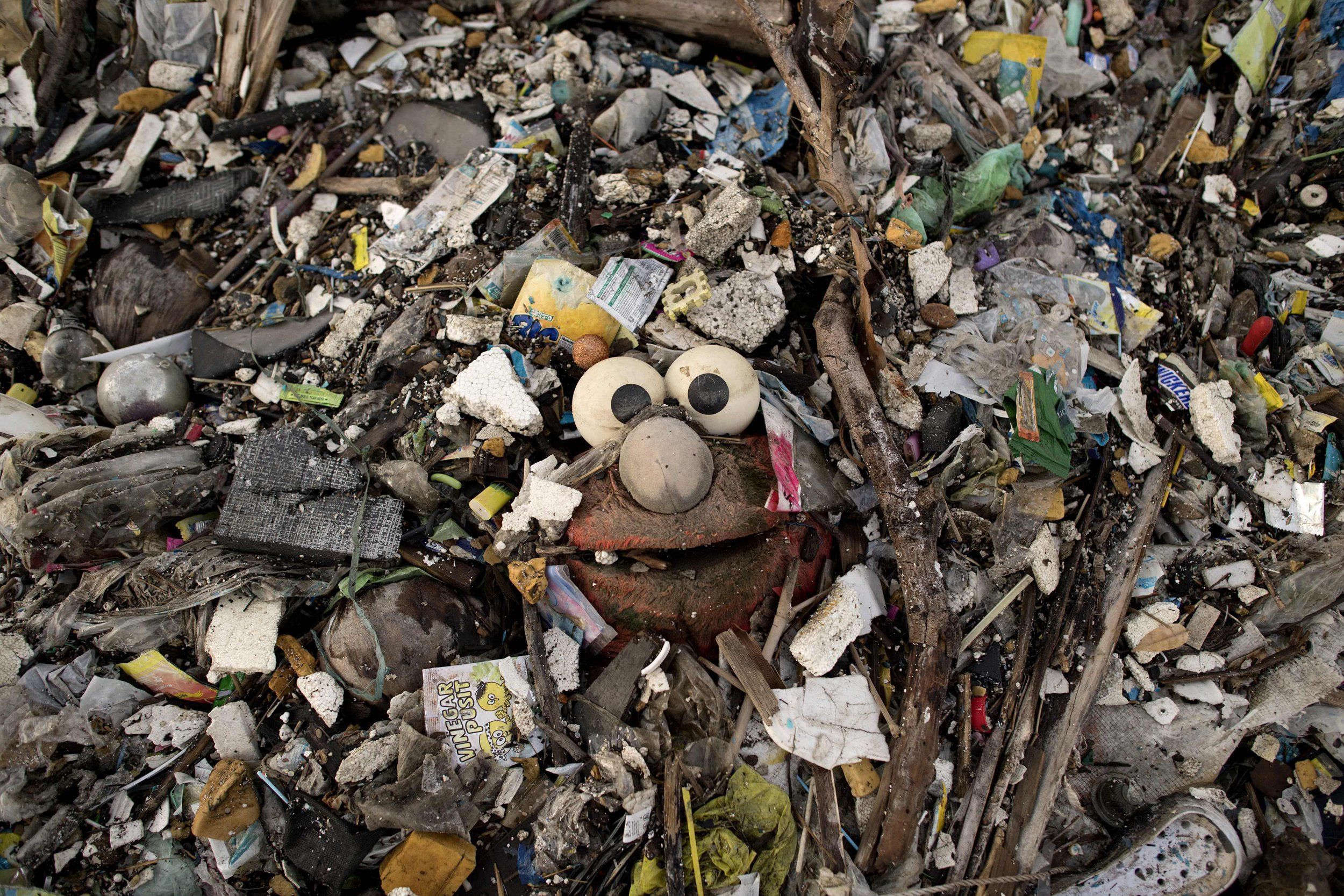 "This photo taken on May 19, 2018 shows a stuffed toy of the Sesame Street character ""Elmo"" surrounded by plastic waste on a beach on the Freedom island critical habitat and ecotourism area near Manila. About eight million tonnes of plastic waste are dumped into the world's oceans every year - the equivalent of one garbage truck of plastic being tipped into the sea every minute... of every day. Over half comes from five Asian countries: China, Indonesia, the Philippines, Thailand and Vietnam, according to a 2015 study in Science journal. / AFP PHOTO / Noel CELISNOEL CELIS/AFP/Getty Images"