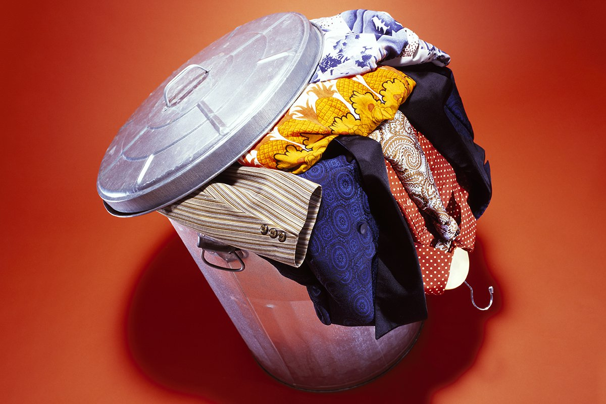 A metal trash can overflowing with used clothing