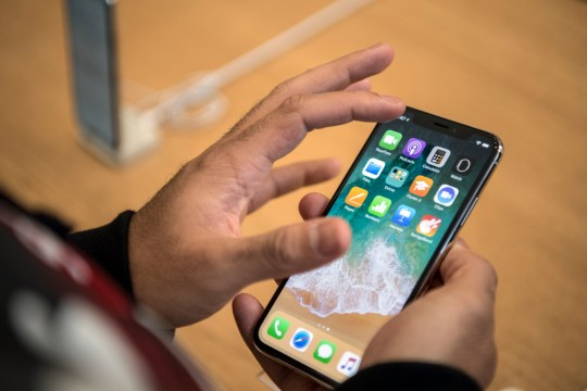 LONDON, ENGLAND - NOVEMBER 03: A customer views the iPhone X upon its release in the U.K on November 3, 2017 in London, England. The iPhone X is positioned as a high-end, model intended to showcase advanced technologies such as wireless charging, OLED display, dual cameras and a face recognition unlock system. (Photo by Carl Court/Getty Images)