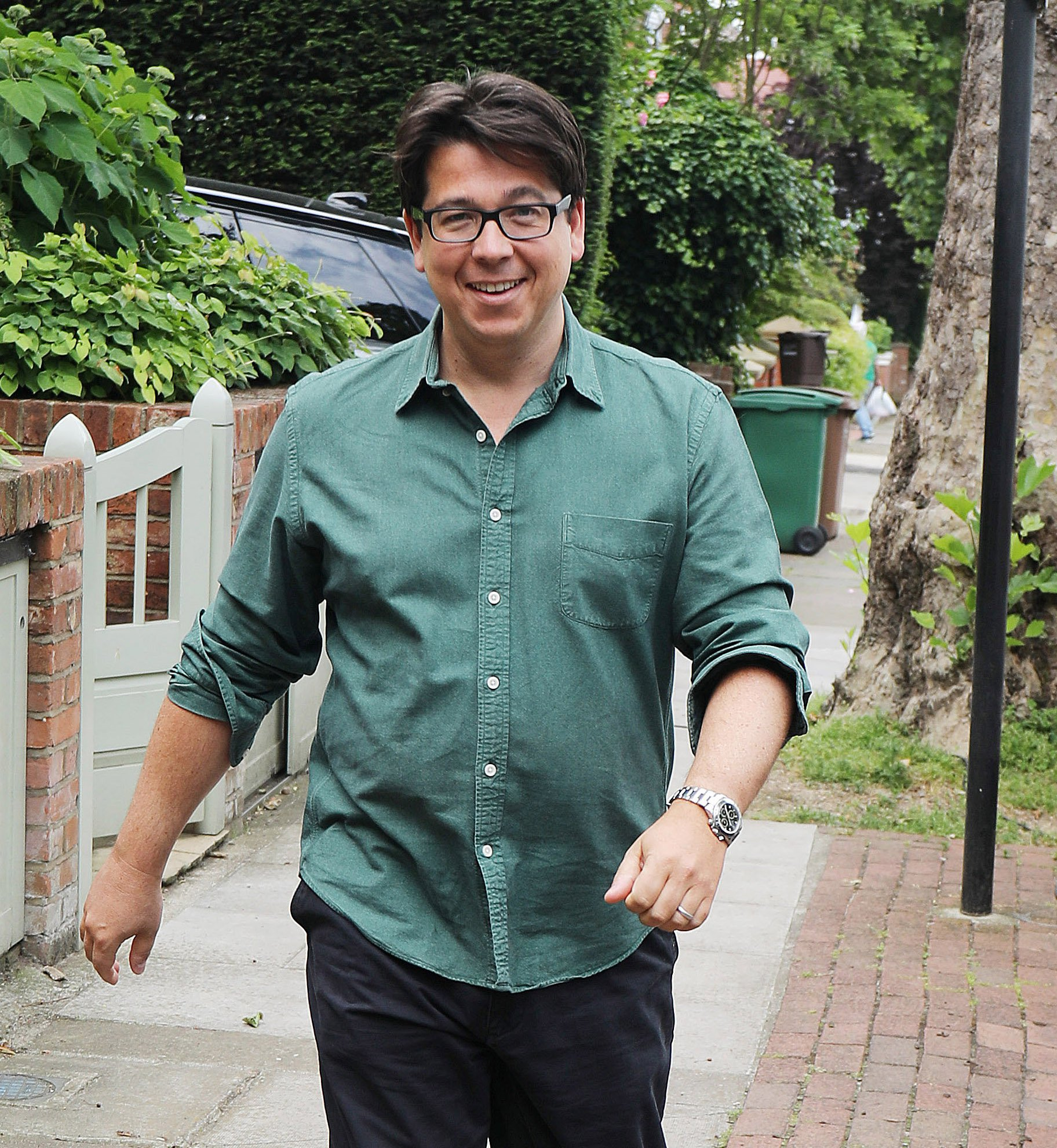 """Pic shows: Michael McIntyre was all smiles as he left home in leafy North London today heading off for his World Tour gig in Dublin. McIntyre was sporting a new watch and smiled broadly as he jauntily strolled to his car. He was using the same car that was brutally attacked earlier in the week, but now he had a driver and a minder in the car with him, possibly for added security. Before stepping into his 120k Range Rover, now repaired, he said to photographers waiting. """"Morning, lads. Drama is all over and now it's back to work. Have a great day."""" pic by Gavin Rodgers/Pixel8000"""