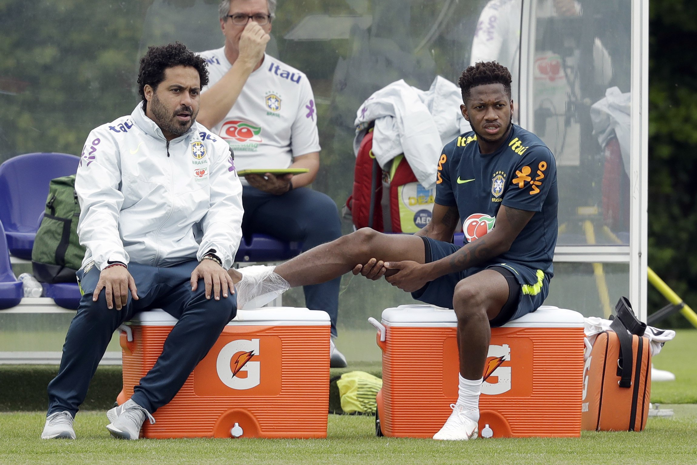 Brazil's Fred sits with an injury to his right ankle from a tackle from Casemiro after walking off the pitch to receive treatment during a national soccer squad training session at the training facilities of Tottenham Hotspur football club in Enfield, England, Thursday, June 7, 2018. (AP Photo/Matt Dunham)