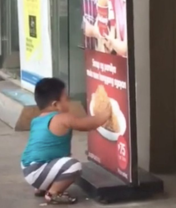 Screen-grab showing three-year-old Harvey Quesa longingly touching a Jolibee's fried chicken poster as he waits for the shop to open, Malasiqui, The Philippines, Sunday 3rd June, 2018. A HILARIOUS video showing a little boy trying to eat the food in a fried chicken advert has gone viral. In the adorable footage, three-year-old Harvey Quesa from Malasiqui, The Philippines stares longingly at a Jolibee's fried chicken poster and attempts to eat pieces of it. The super-cute clip has been viewed over 11 million times since Vince?s cousin, Yna T Devera published it on Facebook on Monday. It has made little Harvey a social media sensation and he has even received free buckets of fried chicken from the advertising fast food chain, Jollibee. The funny incident took place around 5.45am on Sunday 3rd June when Vince was on the way to the market in neighbouring town, Bayambang with his mum and cousin. ... SEE COPY AND VID ... PIC BY NEWS DOG MEDIA ... 0121 517 0019