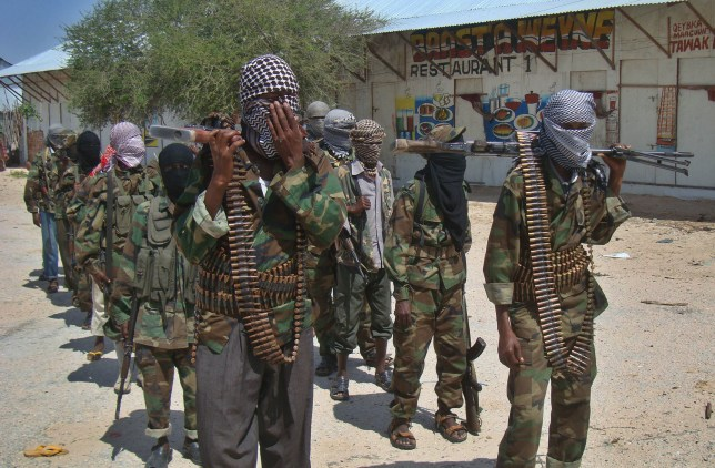 """Al-Qaeda linked al-shabab recruits walk down a street on March 5, 2012 in the Deniile district of Somalian capital, Mogadishu, following their graduation. The walls of the former Shebab base in Baidoa, Somalia, are littered with rudimentary drawings of machine guns and tanks, a note reading """"Fear God, don't write on these walls"""" and a sketch of an Al-Qaeda flag, homage to the rebel group's international allies. The crumbling building is now occupied by Ethiopian troops who nearly two weeks ago forced Shebab rebels out of Baidoa, their former Shebab stronghold and Somalia's third-largest city. AFP PHOTO/Mohamed ABDIWAHAB (Photo credit should read Mohamed Abdiwahab/AFP/Getty Images)"""