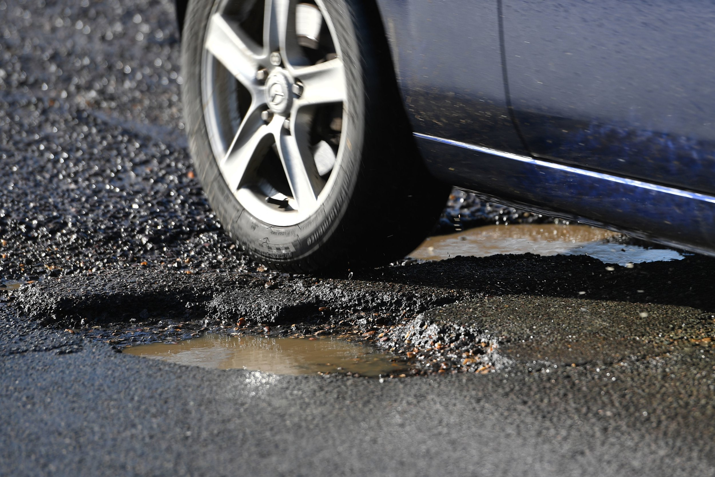 File photo dated 04/04/18 of a car passing a pothole. Britain's road network will in the future be repaired by robots - which can fill in a pothole in a minute. PRESS ASSOCIATION Photo. Issue date: Monday June 11, 2018. See PA story SCIENCE Potholes. Photo credit should read: Joe Giddens/PA Wire