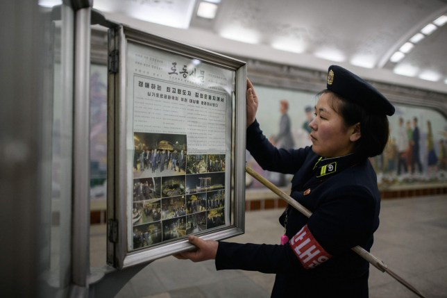 A conductor changes the Rodong Sinmun newspaper showing images of North Korean leader Kim Jong Un in Singapore ahead of his meeting with US president Donald Trump at a news stand on a subway platform of the Pyongyang metro on June 12, 2018. Donald Trump and Kim Jong Un became on June 12 the first sitting US and North Korean leaders to meet, shake hands and negotiate to end a decades-old nuclear stand-off. / AFP PHOTO / ED JONESED JONES/AFP/Getty Images