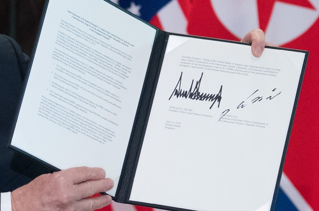 US President Donald Trump holds up a document signed by him and North Korea's leader Kim Jong Un following a signing ceremony during their historic US-North Korea summit, at the Capella Hotel on Sentosa island in Singapore on June 12, 2018. Donald Trump and Kim Jong Un became on June 12 the first sitting US and North Korean leaders to meet, shake hands and negotiate to end a decades-old nuclear stand-off. / AFP PHOTO / SAUL LOEBSAUL LOEB/AFP/Getty Images