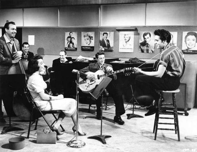HOLLYWOOD - 1957: Rock and roll singer Elvis Presley performs on the set of his film 'Jailhouse Rock' with songwriter Mike Stoller (on piano), Scotty Moore (guitar), Judy Tyler, Bill Black and D.J. Fontana in 1957 in Hollywood, California. (Photo by Michael Ochs Archives/Getty Images)