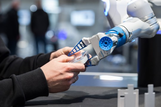 An employee of Festo works with a pneumatic light-weight robot 'Bionic Cobot' at the Hanover Fair ('Hannover Messe')?at the fair grounds in Hanover, Germany, 23 April 2017. 6,500 exhibitors are expected at the world's biggest industrial fair, the Hannover Messe. This year's partnering country is Poland. Photo: Silas Stein/dpa