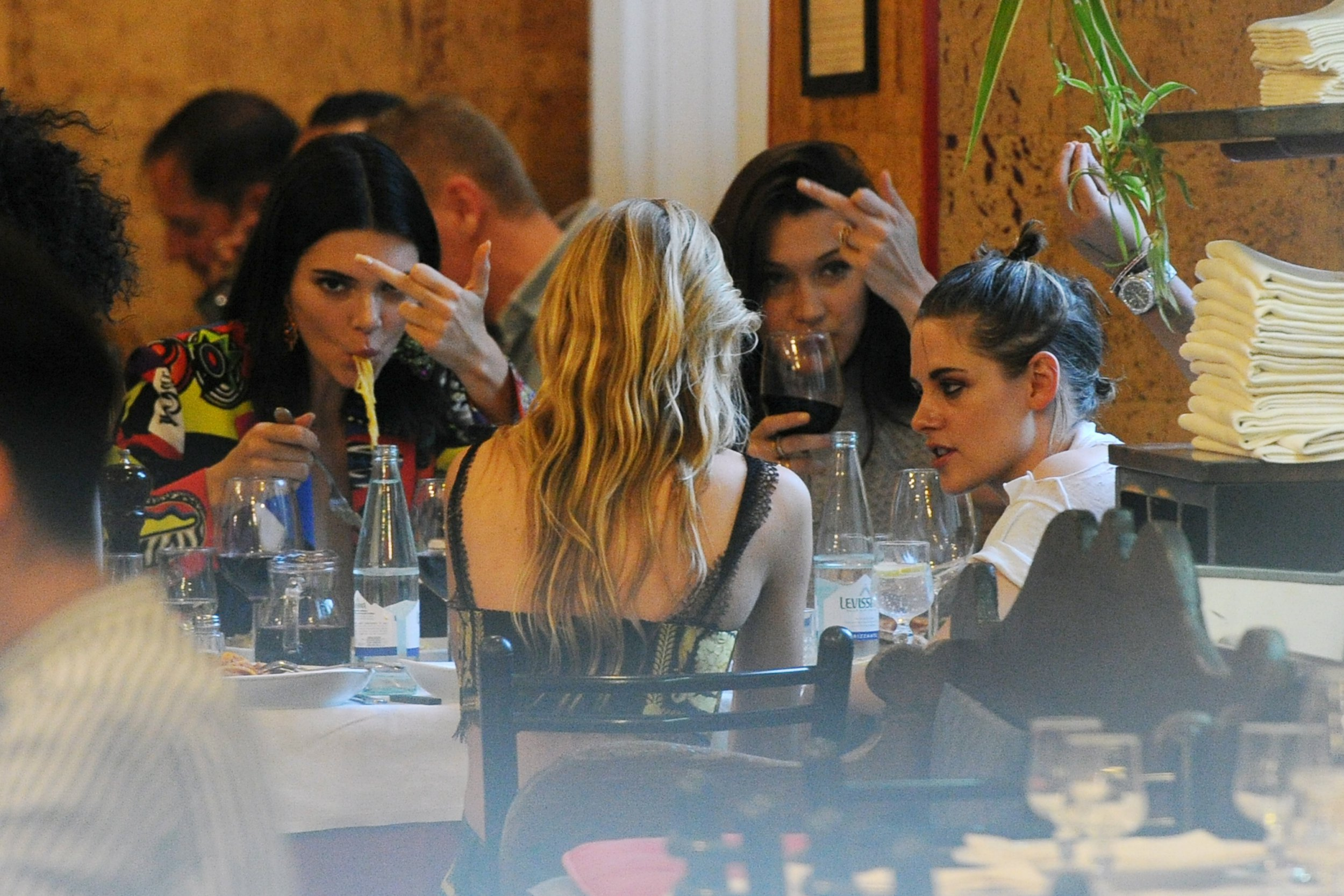 Kendall Jenner and Bella Hadid enjoy pasta, red wine and flipping the bird as they dine with Kristen Stewart
