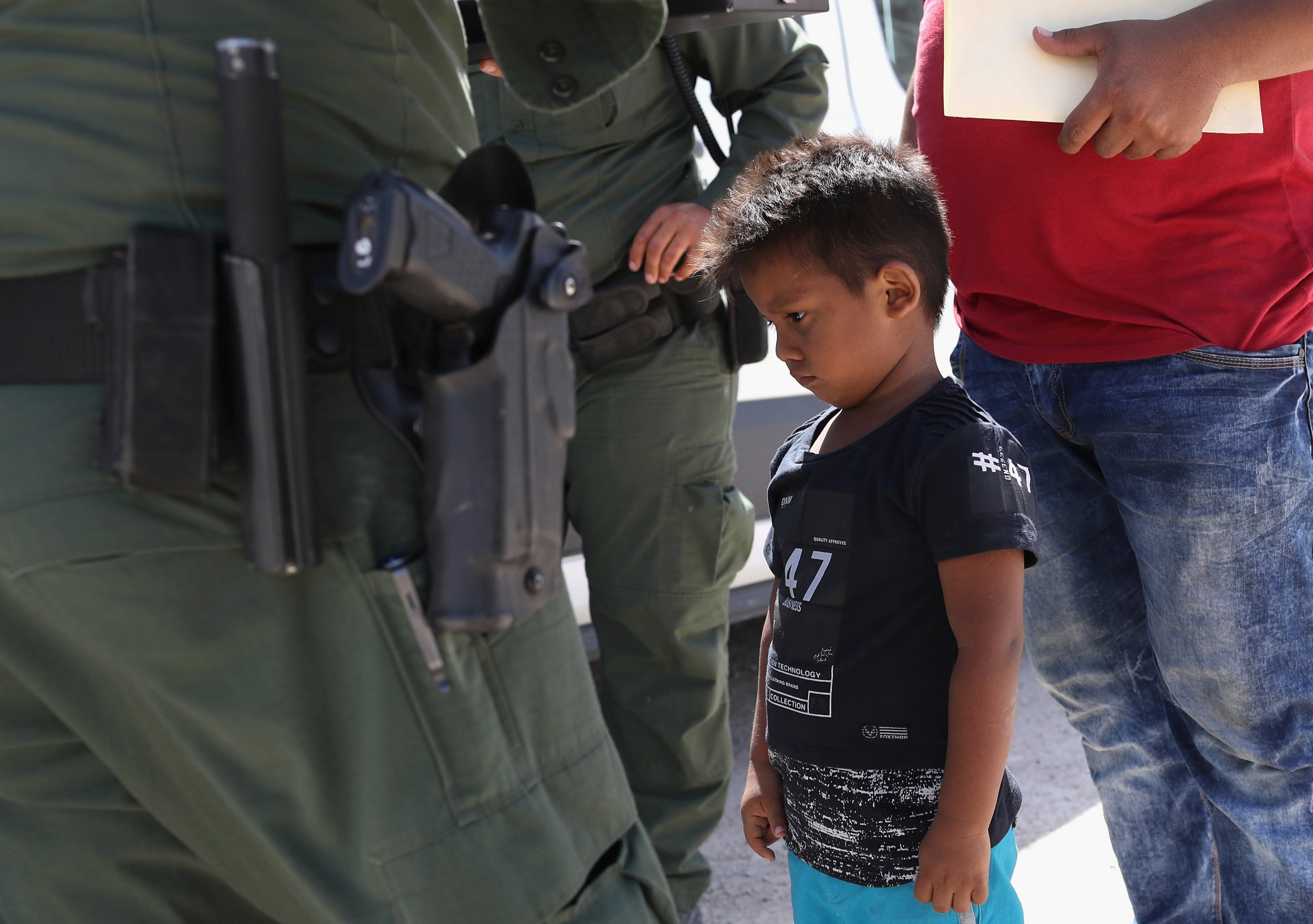 """MISSION, TX - JUNE 12: A boy and father from Honduras are taken into custody by U.S. Border Patrol agents near the U.S.-Mexico Border on June 12, 2018 near Mission, Texas. The asylum seekers were then sent to a U.S. Customs and Border Protection (CBP) processing center for possible separation. U.S. border authorities are executing the Trump administration's """"zero tolerance"""" policy towards undocumented immigrants. U.S. Attorney General Jeff Sessions also said that domestic and gang violence in immigrants' country of origin would no longer qualify them for political asylum status. (Photo by John Moore/Getty Images)"""