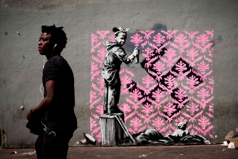 A man walks past a recent artwork by street artist Banksy in Paris on June 24, 2018. / AFP PHOTO / Philippe LOPEZ / RESTRICTED TO EDITORIAL USE - MANDATORY MENTION OF THE ARTIST UPON PUBLICATION - TO ILLUSTRATE THE EVENT AS SPECIFIED IN THE CAPTIONPHILIPPE LOPEZ/AFP/Getty Images