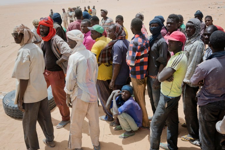 """Migrants and locals wait for trucks arriving from Algeria to unload their cargo on Sunday, June 3, 2018, in order to earn money to pay for the trip north, at a giant desert trading post called """"The Dune"""" in the no-man's land separating Niger and Algeria north of the Assamaka border post in northern Niger. (AP Photo/Jerome Delay)"""